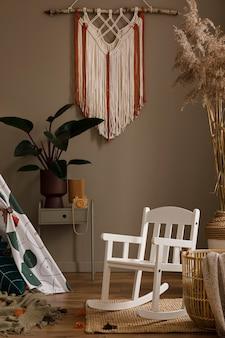 Креативная композиция стильного дизайна интерьера гостиной с деревянными комнатными растениями, висящими украшениями и аксессуарами ретро и винтажная концепция нейтральные стены паркетный пол