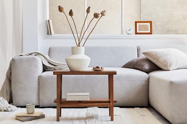 グレーのコーナーソファ、窓、木製のコーヒーテーブル、ドライフラワーの花瓶、身の回り品を備えたスタイリッシュなリビングルームのインテリアのクリエイティブな構成。ベージュのニュートラルカラー。レンプレート。
