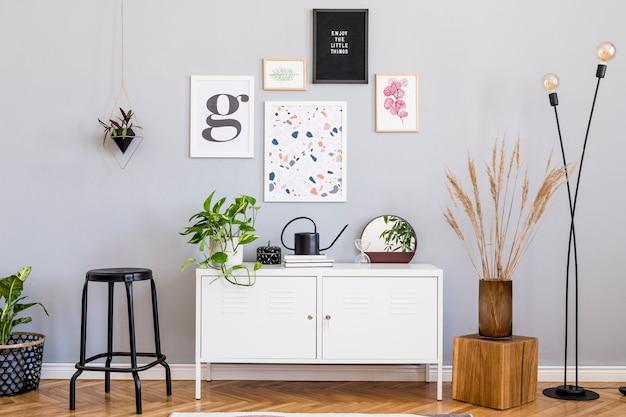 포스터 프레임 나무 옷장 의자 베개 거울 식물 및 액세서리와 세련된 거실 현대적인 인테리어 디자인의 창조적 인 구성. 중립 벽 쪽모이 세공 마루
