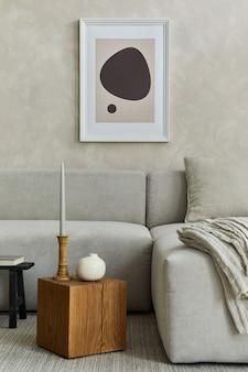 모의 포스터 프레임, 회색 소파, 나무 큐브 및 작은 개인 액세서리가 있는 세련된 현대적인 거실의 창의적인 구성. 창의적인 벽과 쪽모이 세공 마루 바닥. 세부. 주형.