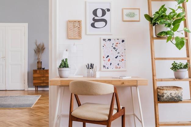 Креативная композиция стильного дизайна интерьера домашнего офиса scandi с рамами, деревянным столом, стулом, растениями и аксессуарами. стены нейтральные, пол паркет.