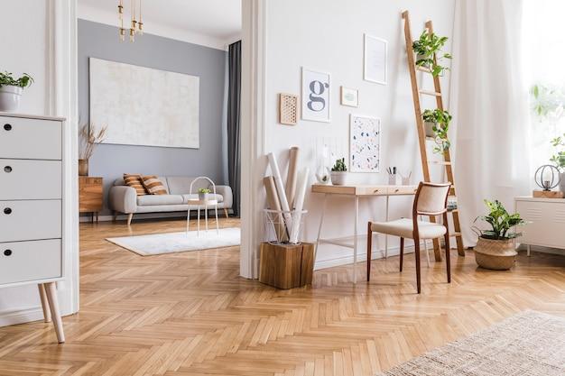 モックアップポスターフレーム、木製の机、椅子、植物、アクセサリーを備えたスタイリッシュなスカンジホームオフィスのインテリアデザインの創造的な構成。中立的な壁、寄木細工の床。テンプレート。