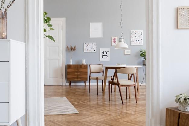 モックアップポスターフレーム、木製の箪笥、椅子、植物、アクセサリーを備えたスタイリッシュなスカンジリビングルームのインテリアデザインの創造的な構成。中立的な壁、寄木細工の床。テンプレート。