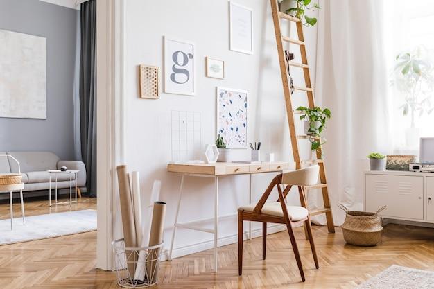 포스터 프레임, 나무 책상, 의자, 식물 및 액세서리가있는 세련된 스칸디나비아 홈 오피스 인테리어 디자인의 창의적인 구성. 중립 벽, 쪽모이 세공 마루 바닥.