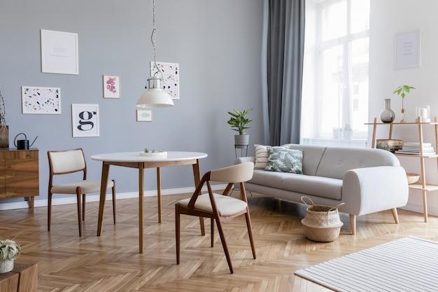 포스터 프레임, 소파, 나무 옷장, 의자, 식물 및 액세서리가있는 세련된 스칸디나비아 거실 인테리어 디자인의 창의적인 구성. 중립 벽, 쪽모이 세공 마루 바닥.