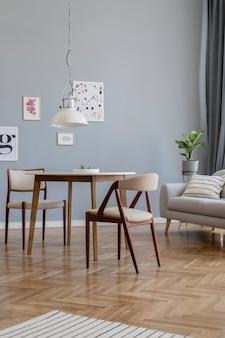 포스터 프레임, 소파, 나무 옷장, 의자, 식물 및 액세서리가있는 세련된 scandinaviannavian 거실 인테리어 디자인의 창의적인 구성. 중립 벽, 쪽모이 세공 마루 바닥.