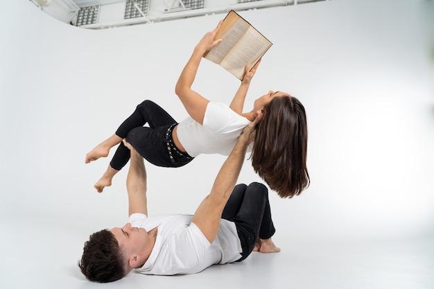 Творческий состав женщины, лежащей на руках человека и чтения книги. концепция поддержки, ухода и образования.