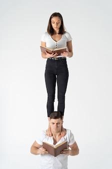 Творческая композиция женщины, стоящей на плечах мужчины и читающей книгу
