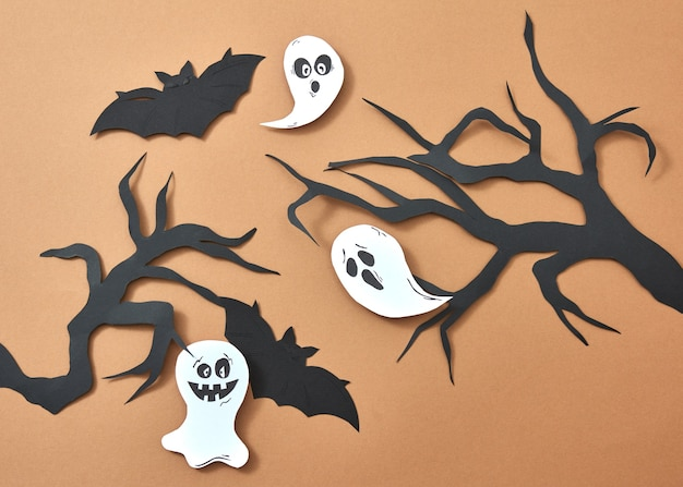 Creative composition of paper with flying bats and ghosts over tree branches on a brown background with space for text. handcraft layout for halloween. flat lay