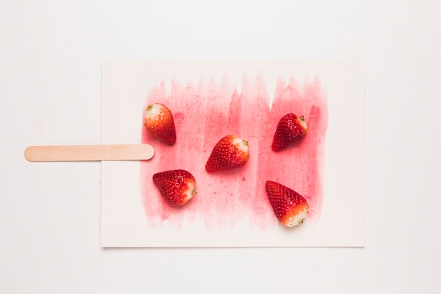 Creative composition of popsicle from fragrant strawberry on stick