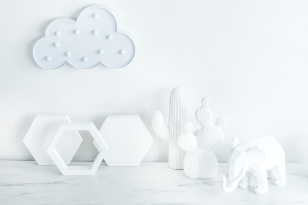 Creative composition in scandinavian style with cloud on the white wall, geometric shape accessories and white figures of cacti and elephant. white minimalistic concept. copy space. template.