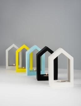 창의적인 구성. 정물. 집 모양의 콘크리트 촛대 흰색, 검정색, 회색, 파란색 밴딩 노란색 색상으로 소이왁스를 태우는 향초. 미니멀리즘