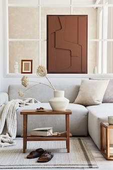 Creative composition of stylish and cozy living room interior with mock up structure painting, grey corner sofa, window, coffee table and personal accessories. beige neutral colors. template.