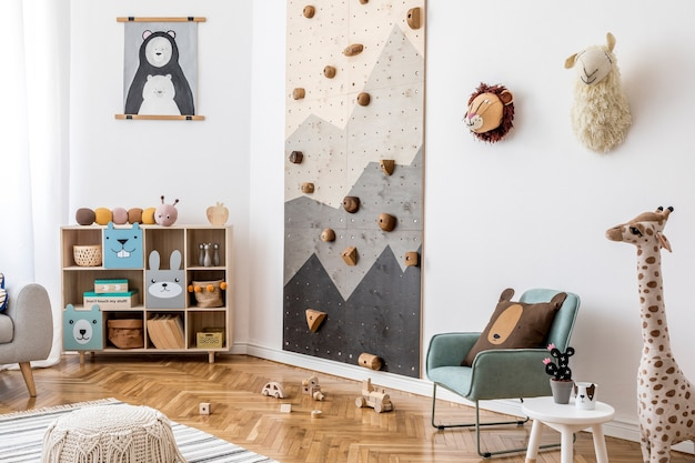 Creative composition of stylish and cozy scandi child room interior design with graphic on the wall toys and plush toys sofa commode armchair carpet and accessories white wall and parquet floor
