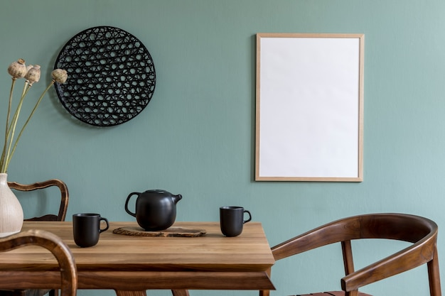 Creative composition of stylish scandi dining room interior with frame, wooden table, chair, plant and accessories. eucalyptus walls.