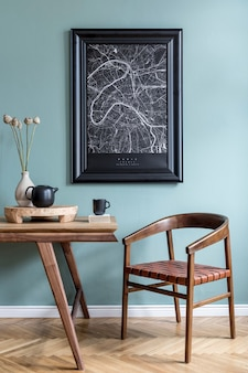 Creative composition of stylish scandi dining room interior with map frame, wooden table, chair, plant and accessories. eucalyptus walls, parquet floor.