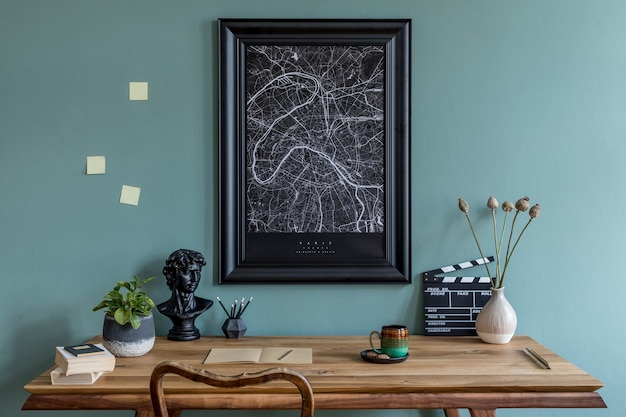 Creative composition of stylish scandi dining room interior with map frame, wooden table, chair, plant and accessories. eucalyptus walls.