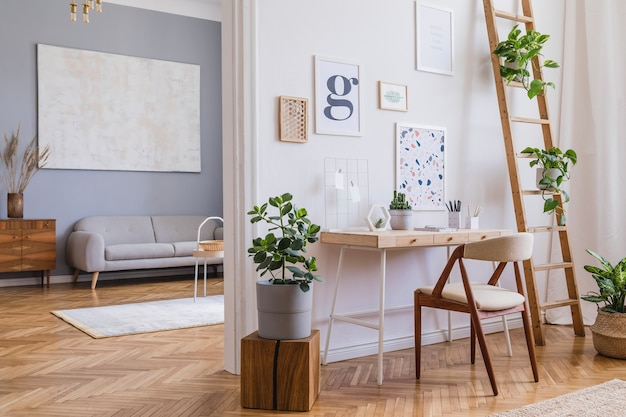 Creative composition of stylish scandi home office interior design with frames, wooden desk, chair, plants and accessories. neutral walls, parquet floor.