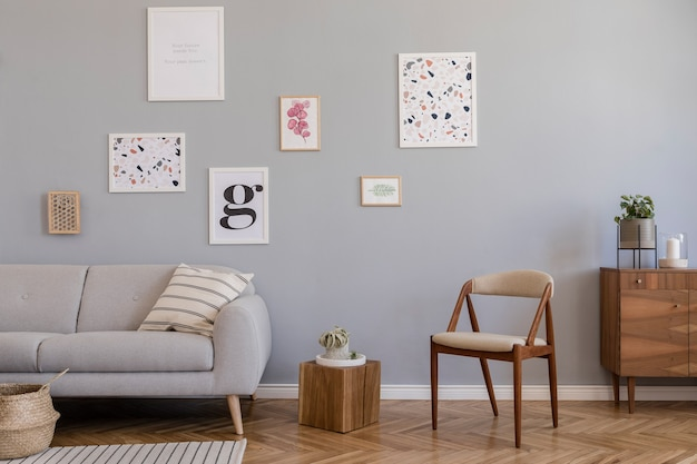 Creative composition of stylish scandi living room interior design with frames, sofa, wooden commode, chair, plants and accessories. neutral walls, parquet floor.