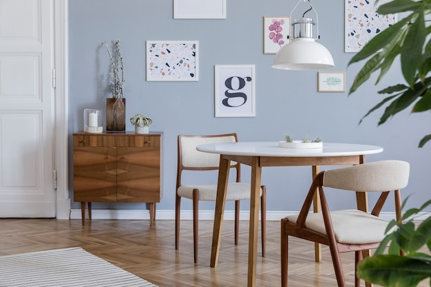 Creative composition of stylish scandi living room interior design with frames, wooden commode, chair, plants and accessories. neutral walls, parquet floor.