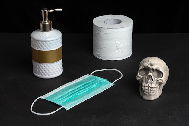 黒いテーブルの上にハンドソープとトイレットペーパーと頭蓋骨を使ったクリエイティブな構図。