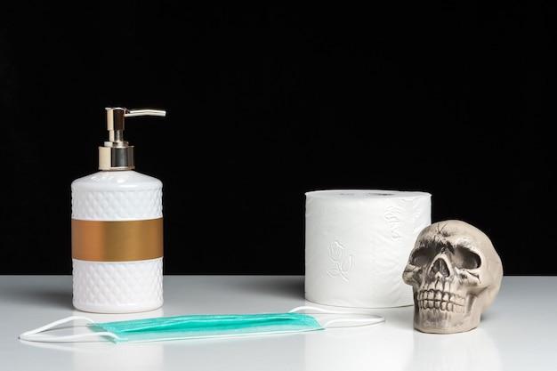 白いテーブルの上にハンドソープとトイレットペーパーと頭蓋骨を使ったクリエイティブな構成。