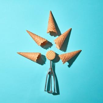 アイスクリーム用の金属スプーンとハードシャドウのある青い背景のワッフルコーンを使用したクリエイティブな構成。フードモダンスタイル。上面図。