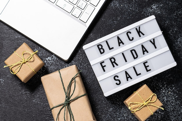 Creative composition with black friday sale text on the lightbox, laptop and gift boxes in craft paper on black rustic background. online shopping concept.
