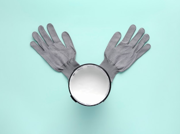 Creative composition with can of white paint and work gloves on pastel blue