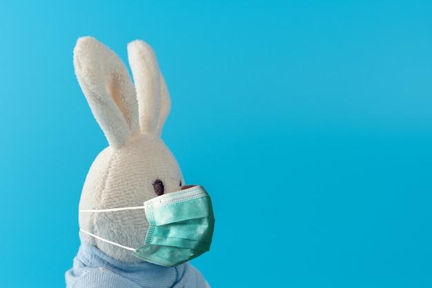 ウイルスマスク付きのかわいいバニー人形との創造的な構成。