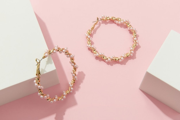 Creative composition with earrings on pink background trendy jewelry in minimalist style
