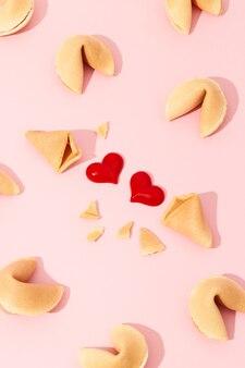 분홍색 배경에 포춘 쿠키와 하트가 있는 창의적인 구성