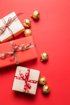 Creative composition with gifts or presents boxes, gold bowson red background.