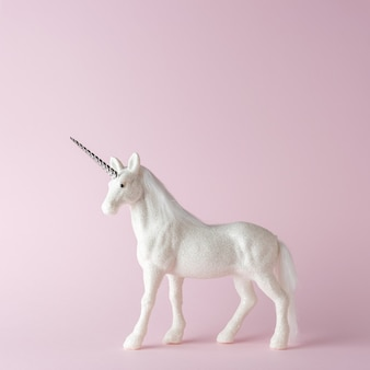 Creative composition with glitter unicorn on pink background