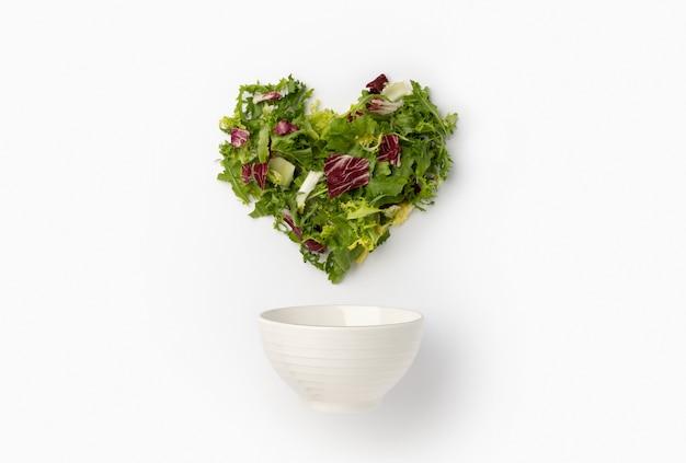 Креативная композиция с листьями салата в форме сердца и керамической миской