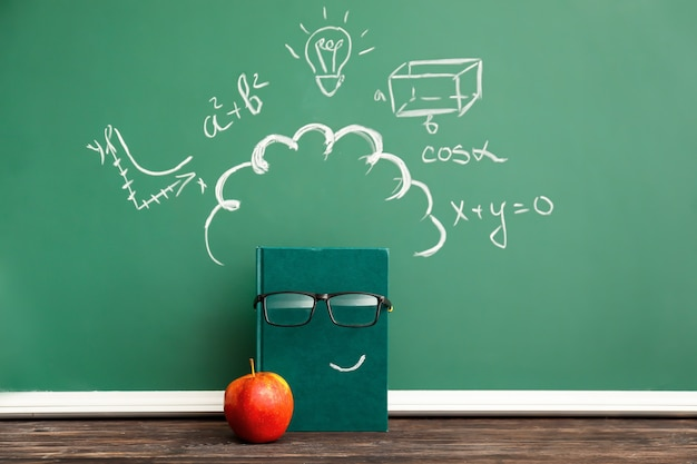 Creative composition with notebook, apple and school blackboard