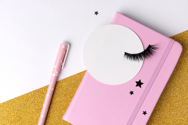 Creative composition with notepad and eyelashes on pink golden glitter background