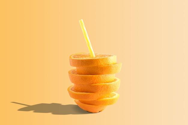 明るい背景にオレンジジュースとわらの創造的な構成
