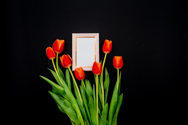 Creative composition with photo frame mockup, red tulips