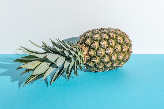Творческая композиция с ананасом на синем фоне.