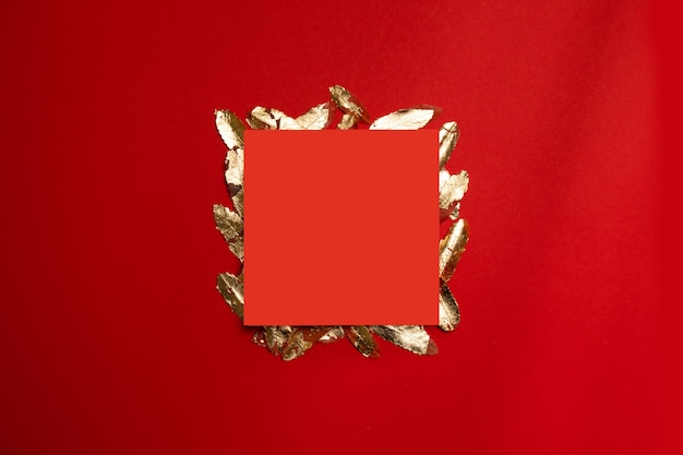 Creative composition with red leaf frame with gold leaves on a red background.