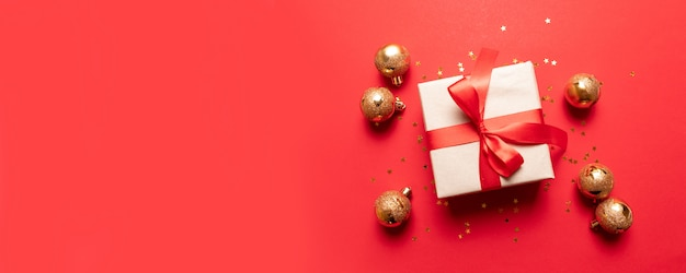 Creative composition with red present box, ribbons, red gold big and small balls, holiday decorations on red background.