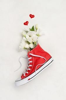 Творческая композиция с красными кроссовками и цветами на белом фоне. день рождения женский день день матери поздравительная открытка.