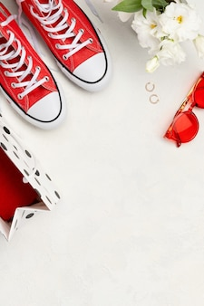 Creative composition with red sneakers, cosmetics and accessory