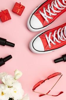 赤いスニーカー、化粧品、ピンクの背景のアクセサリーと創造的な組成物。誕生日女性の日母の日グリーティングカード。
