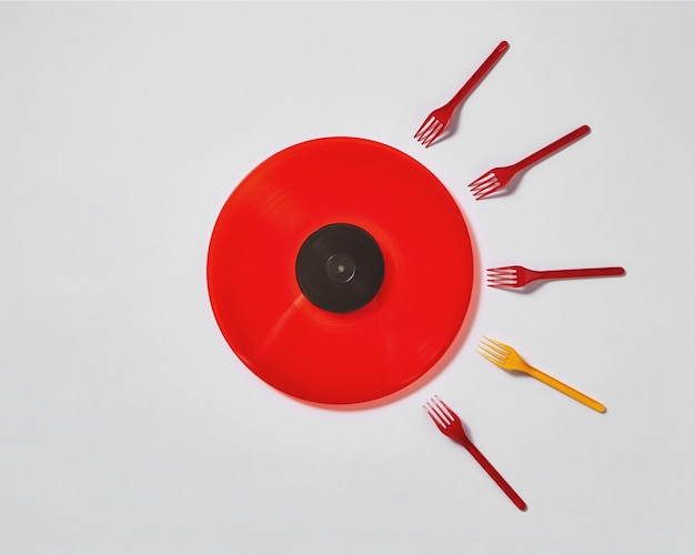 Creative composition with red vinyl record and plastic colored forks