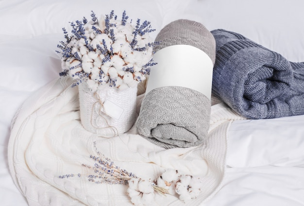 Creative composition with rolled blankets, cotton and lavender flowers