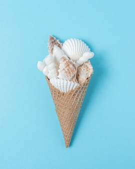 Творческая композиция с ракушками и рожком мороженого на пастельно-синем фоне.