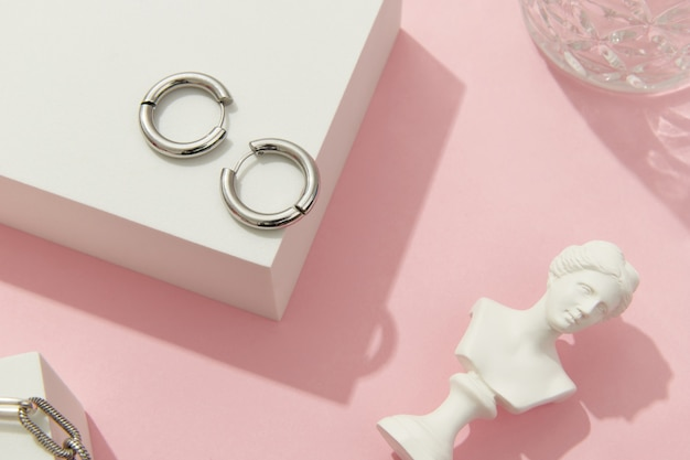 Creative composition with silver jewelry set on pink background trendy accessories in minimalist style