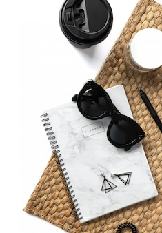 Creative composition with sunglasses, planner, cosmetics and straw napkin on white background
